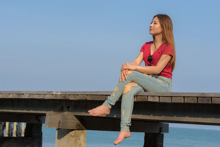 Woman sitting on railing against sky