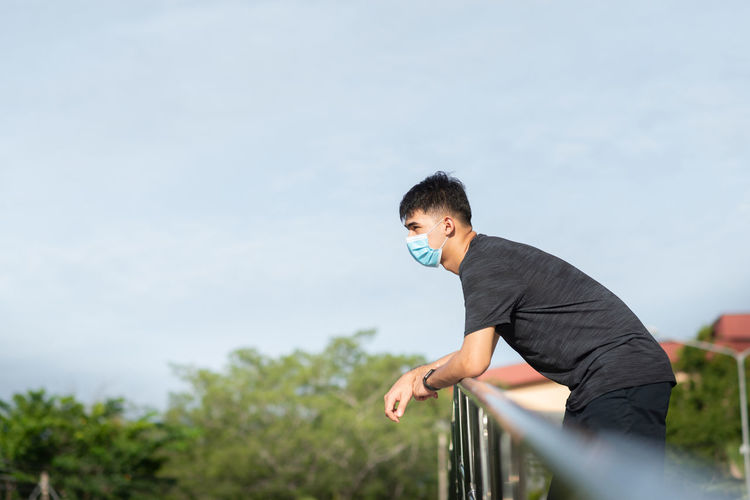 Side view of young man looking away standing by railing against sky