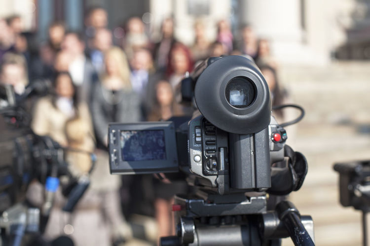 Close-up of television camera against people