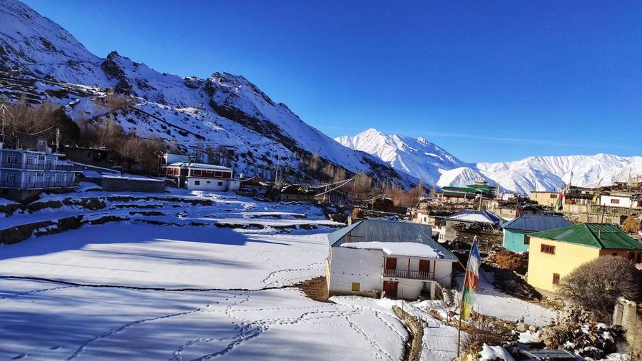 Snow covered houses by buildings against clear blue sky