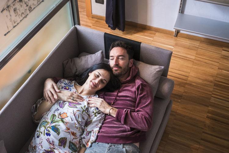 High angle view of couple lying down on sofa at home