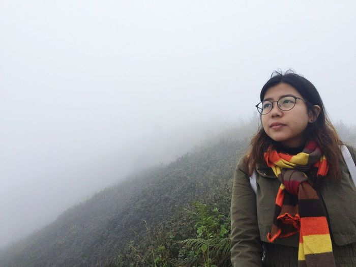 Thoughtful Woman Looking Away While Standing On Mountain During Foggy Weather