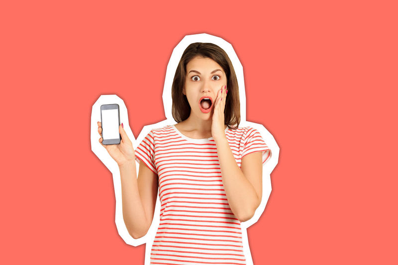 Young woman using smart phone against red background