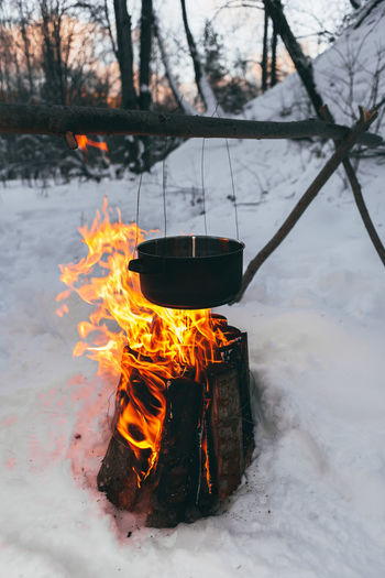 Iron pot, boiling water outside, winter time. Bonfire Burning Day Fire - Natural Phenomenon Fire Pit Flame Heat - Temperature Nature No People Outdoors Snow Tree Winter