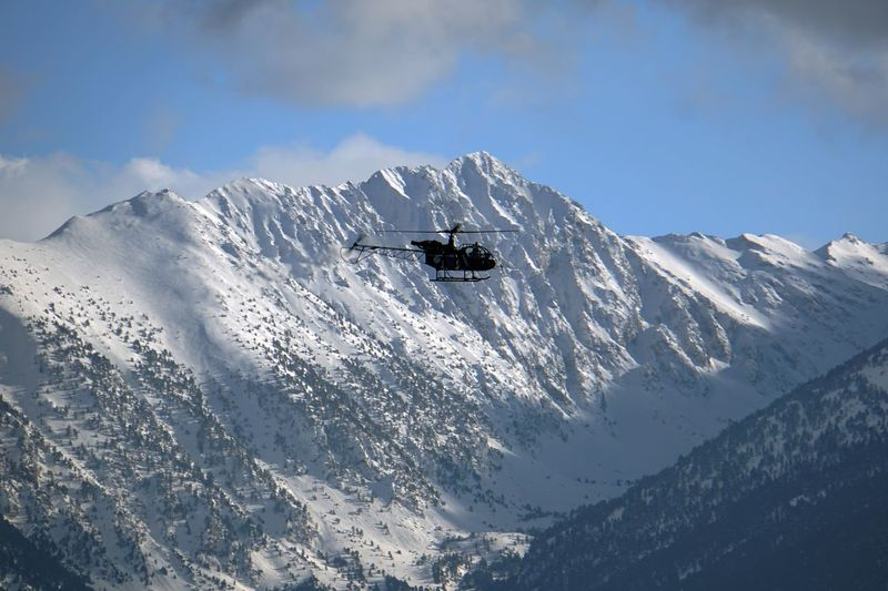 Helicopter flying over snowcapped mountain
