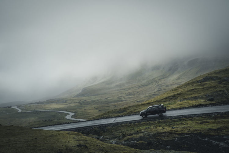 The way to Norðradalur - a small village on the west coast of Streymoy. Location: Norðradalur, Faroe Islands Equipment: Fujifilm X-T2 + XF18-55 F2.8-4 www.instagram.com/nils_leithold Beauty In Nature Car Day Faroe Islands Fog Foggy Green Jeep Landscape Moody Mountain Mountain Range Mountain Road Nature No People Norðradalur Outdoors Road Scenics Sky Street SUV The Great Outdoors - 2017 EyeEm Awards Transportation Winding Road Be. Ready.