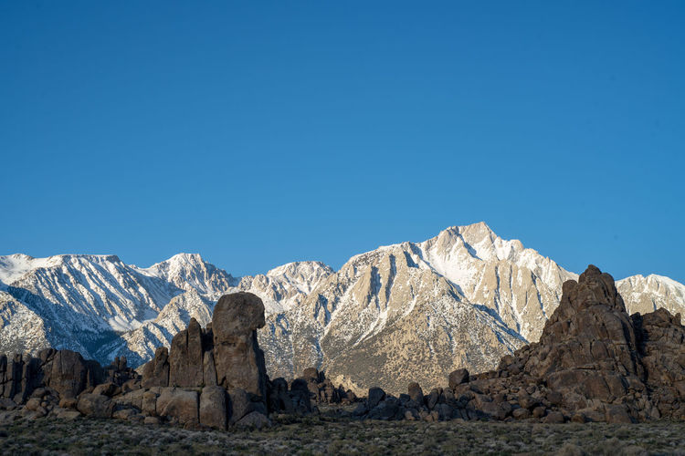 rock formations in front of snowy peaks of Sierra Nevada mountains in Lone Pine, California, USA Mountain Clear Sky Scenics - Nature Sky Beauty In Nature Copy Space Blue Mountain Range Tranquil Scene Rock Tranquility Non-urban Scene Solid Nature Environment Day No People Snowcapped Mountain Formation Climate Mountain Peak Alabama Hills, CA Sierra Nevada Mountains Rock Formations