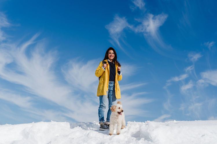 Woman with dog on snow against sky