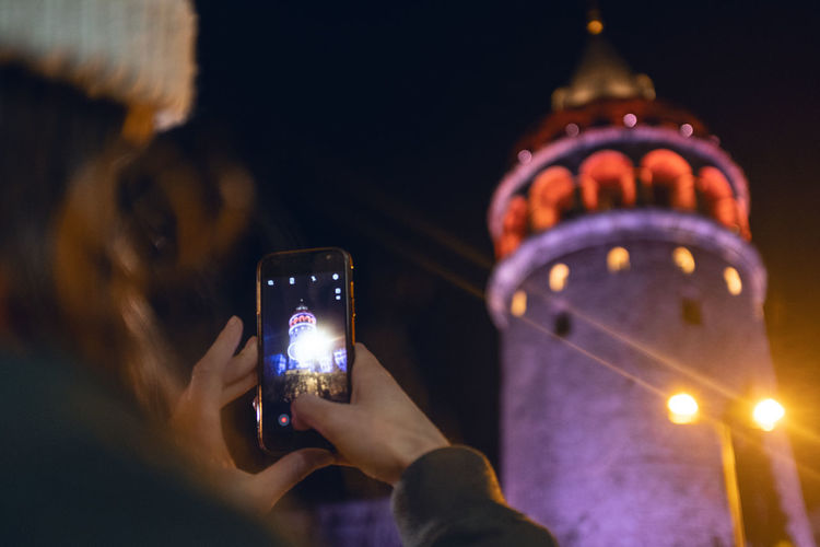 Galata Tower Smart Phone Wireless Technology Technology Portable Information Device Photographing Illuminated Mobile Phone Photography Themes Communication Holding Connection Human Hand Activity Photo Messaging Night Selective Focus One Person Architecture Real People Telephone Hand Night Lights