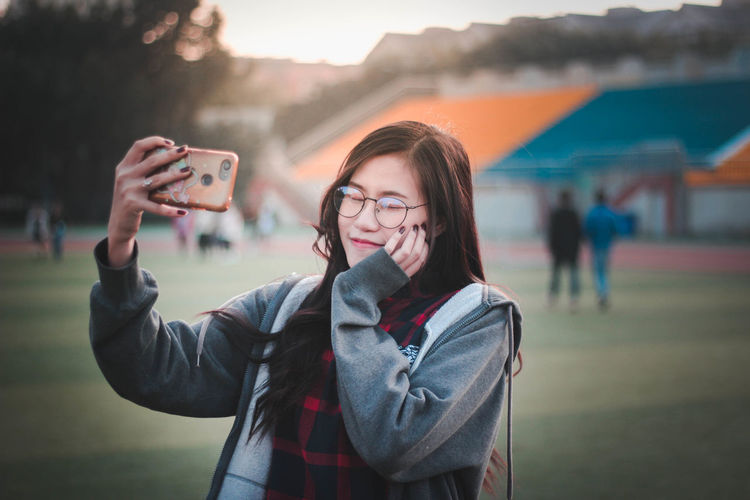 Smiling young woman taking selfie while standing outdoors