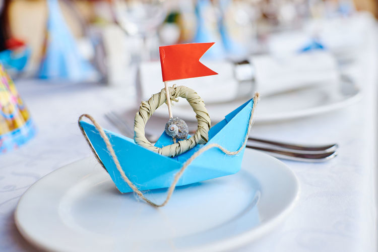 Close-up of paper boat in plate on table