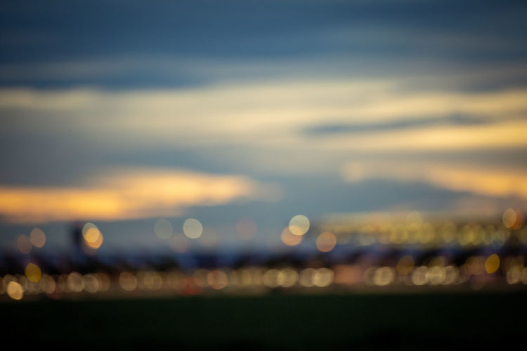 Defocused image of illuminated city against sky during sunset