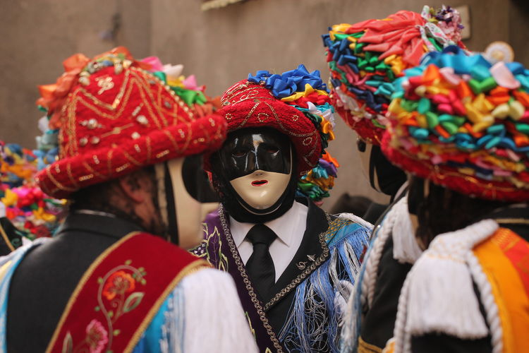 People wearing mask and traditional clothing during carnival on road