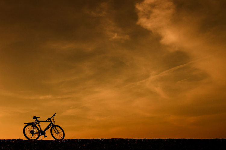 Silhouette bicycle against sky during sunset