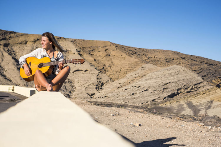 Smiling young woman with guitar sitting on retaining wall by beach