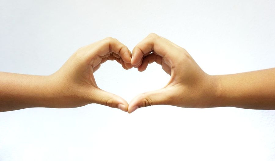 Close-up of hands making heart shape against white background