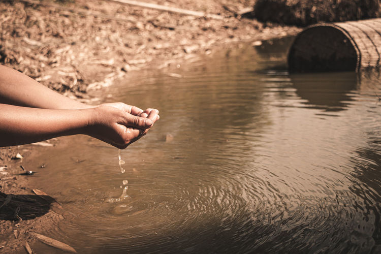 Person hand on rock in river