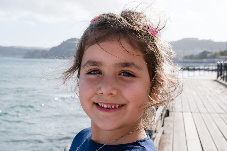 Close-Up Portrait Of Smiling Girl At Jetty By Sea
