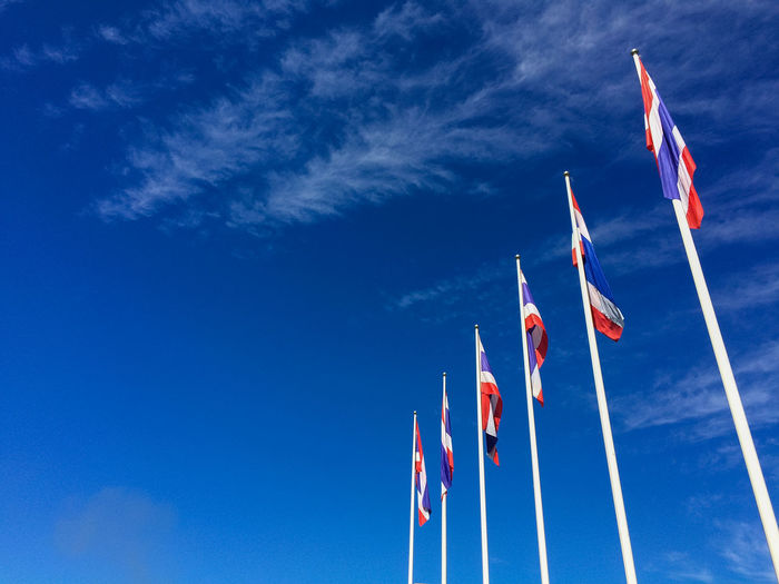 Low Angle View Of Thai Flags In Row Against Blue Sky