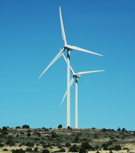 Low angle view of wind turbines on field against clear blue sky