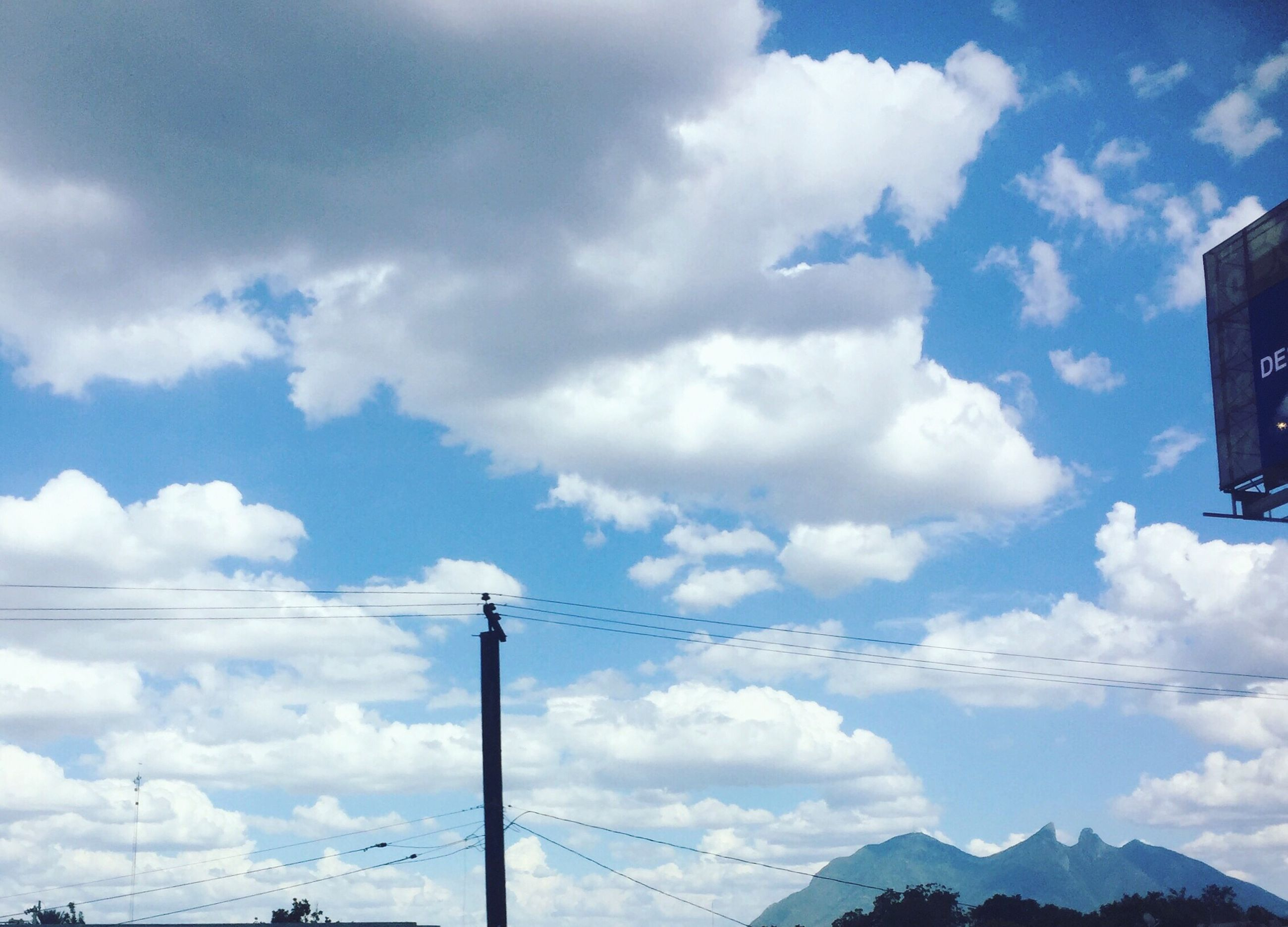 sky, cloud - sky, mountain, power line, low angle view, cloudy, cloud, cable, power supply, scenics, tranquility, beauty in nature, nature, mountain range, weather, tranquil scene, landscape, day, blue, outdoors, power cable, no people, cloudscape, pole, non-urban scene, idyllic, overcast