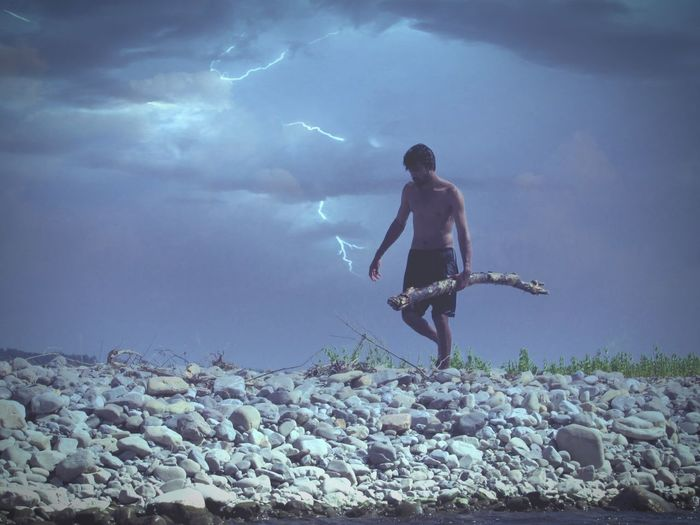Full length of shirtless man carrying log on rocks against cloudy sky