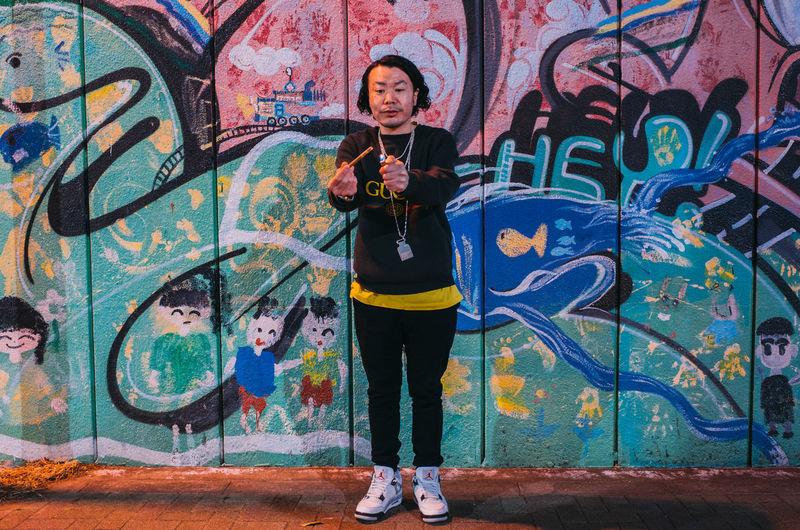 Full length portrait of man standing against graffiti wall