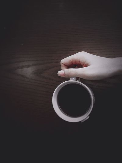Cropped Image Of Woman Holding Black Coffee Cup On Table At Cafe