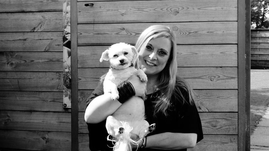 Portrait of smiling woman carrying dog while standing against wooden wall