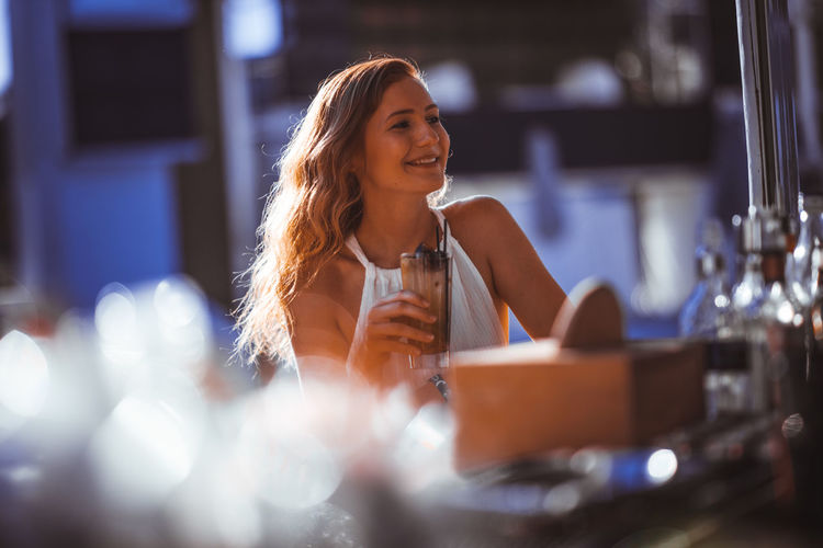 Young Woman Having Drink At Sidewalk Cafe