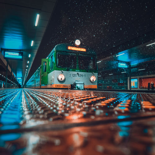 Train on illuminated railroad station at night