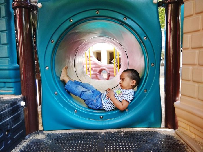 Side view full length of boy lying down in tunnel slide