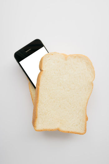 High angle view of bread with knife against white background