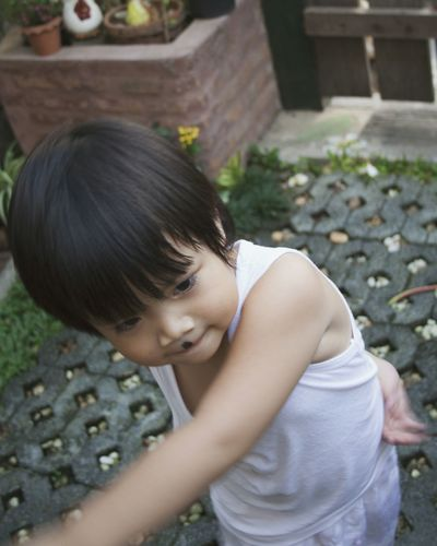 High angle view of boy playing while standing in yard