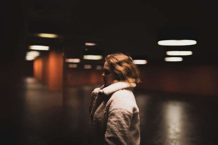 Young woman looking away while standing in garage