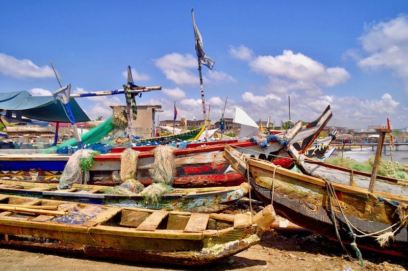Fishing boats moored at harbor against sky