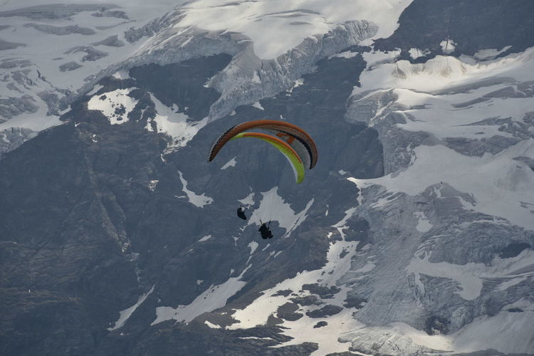 Person paragliding over snowcapped mountain