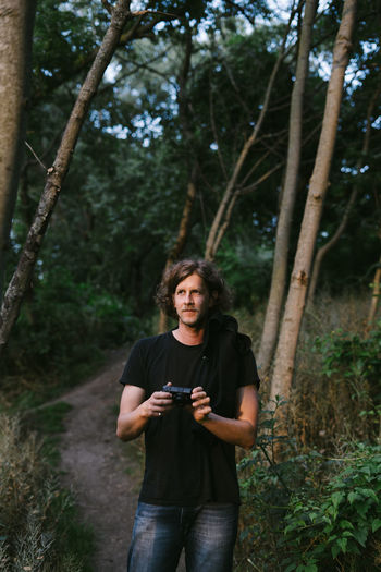 Portrait of young man using camera in forest