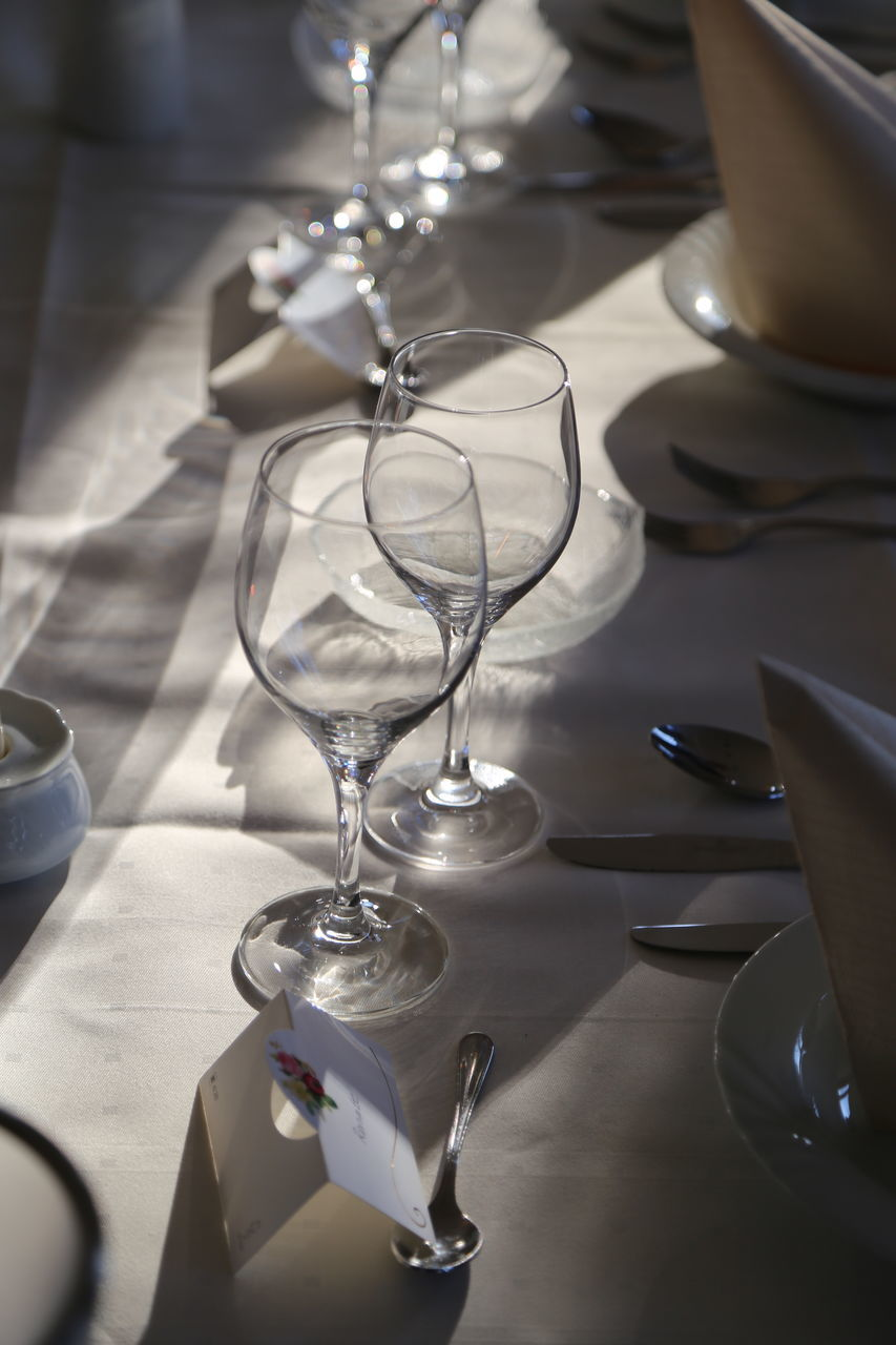 table, indoors, wineglass, glass, no people, still life, glass - material, food and drink, household equipment, drink, drinking glass, close-up, high angle view, refreshment, transparent, business, place setting, setting, restaurant, focus on foreground, table knife, dining