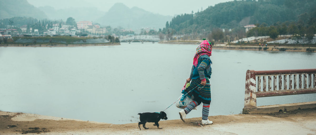Side view of woman with dog walking by lake