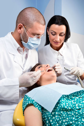 Male dentist with assistant and patient at dental clinic Dental Dentist Dentistry Man Medicine Nurse Office Uniform Work Attractive Caucasian Dental Clinic Friendly Healthcare And Medicine Indoors  Job Medical Occupation Orthodontic Orthodontist  Patient Procedure Professional Occupation Teeth Tooth