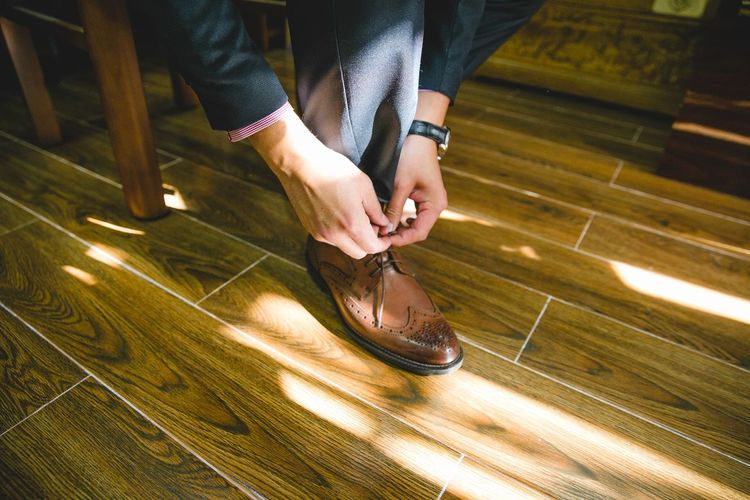 Low section of businessman tying shoe