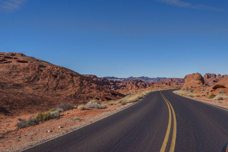 Empty Road Amidst Desert Against Clear Blue Sky