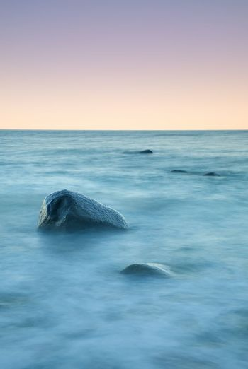Romantic atmosphere in peaceful morning at sea. big boulders sticking out from smooth wavy sea.