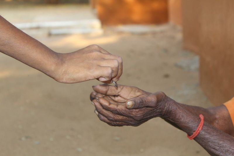 Cropped Hand Giving Coin To Female Beggar On Footpath