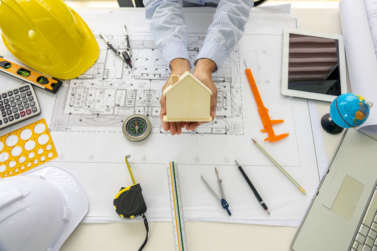 Cropped hand of architect holding model home over blueprint at desk