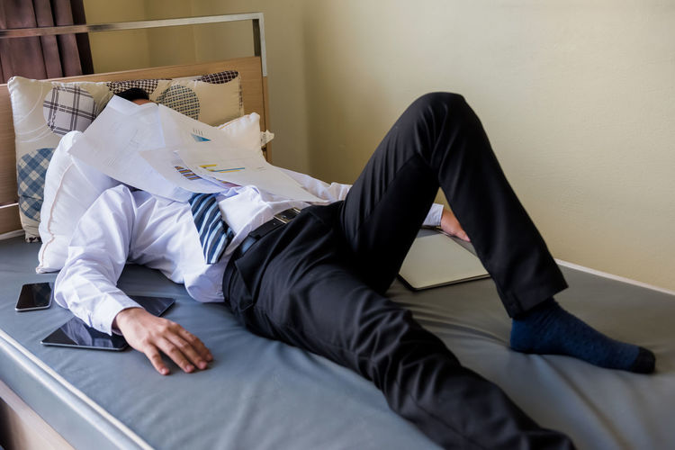 Midsection of man sleeping on bed at home