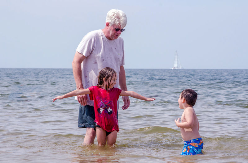 Grandfather playing with grandchildren in the water