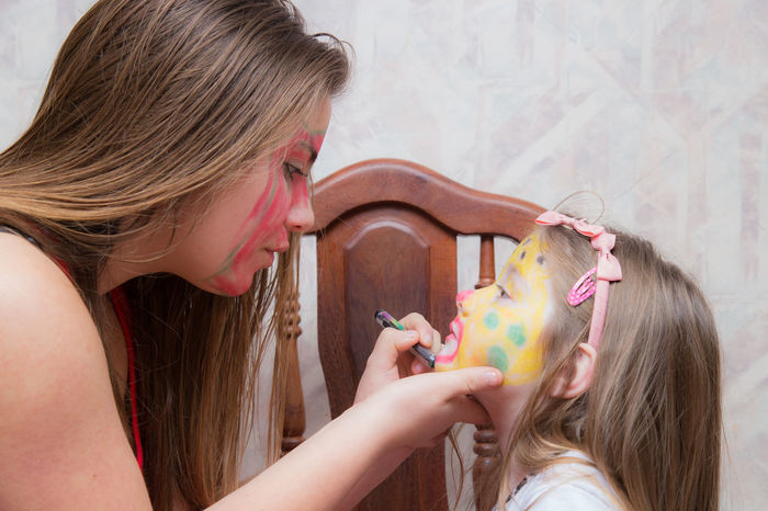 Face Painting Blond Hair Body Painting Bonding Casual Clothing Child Childhood Close-up Day Enjoyment Face Paint Face Painted Child Fun Girls Happiness Headshot Holding Indoors  Leisure Activity Lifestyles Long Hair People Real People Togetherness Two People Visual Creativity