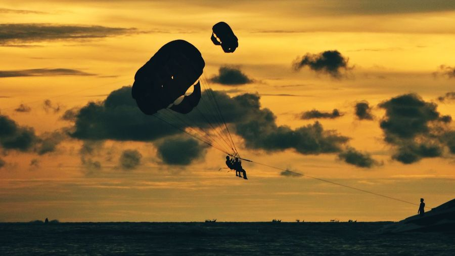 Fly Sky Sunset Silhouette Orange Color Mid-air Cloud - Sky Nature Water Sport Scenics - Nature Leisure Activity Outdoors Flying Beauty In Nature Adventure Parachute Lifestyles Parasailing Extreme Sports Transportation